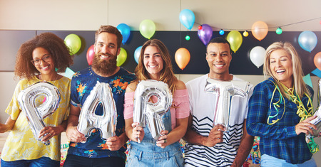 merrymaking: Friends holding balloons as letters for PARTY in room with balloons in background Stock Photo