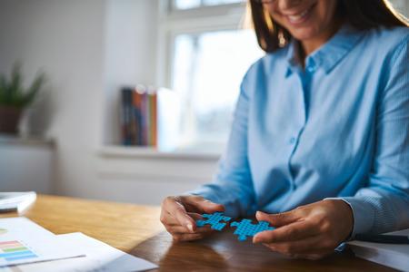 Selectieve aandacht close-up van de vrouw aan de balie assembleren twee puzzelstukken voor concept over ondernemers mensen het oplossen van problemen