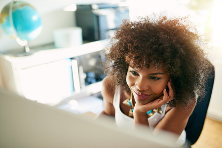 Happy satisfied young businesswoman reading data on her desktop computer with a broad grin , high angle close up view