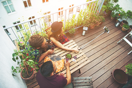 merrymaking: Overhead view of three friends on patio taking photo using device with long attachment