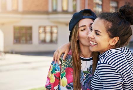 Hartelijke trendy jonge vrouw die haar lachende vriend op de wang kust aangezien zij zich aan de kant van een stedelijke straat met exemplaarruimte bevinden