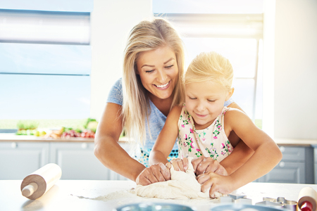 adoring: Adoring young mother teaching her daughter to bake as they stand together at the kitchen table kneading the dough for cookies