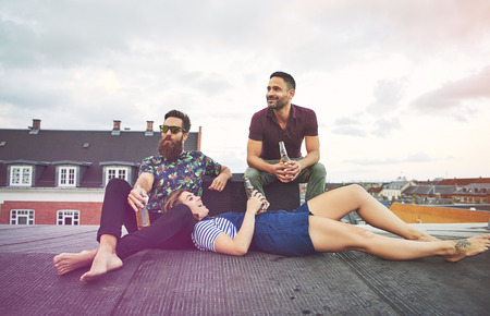 merrymaking: Singing young woman laying in lap of bearded man near friend on roof in European city drinking bottles of beer Stock Photo