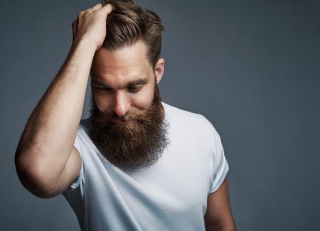 Denken jonge man met een lange baard en een wit shirt met haar tijdens het naar beneden gericht over grijze achtergrond met een kopie ruimte