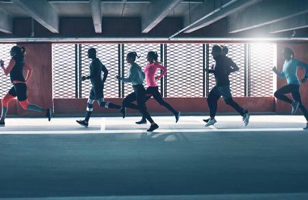 지하 주차장의 창문에 밝게 불이 붙은 눈금 앞에서 달리고있는 다양한 젊은이들의 그룹