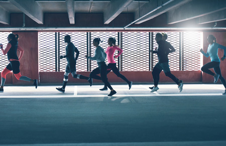 Group of diverse young people urban running in front of the brightly lit grids on the windows of an undercover parking lot Banco de Imagens