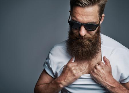 hombre con barba: hombre de barba larga única en gafas de sol mostrando su pecho tirando abajo a la camisa blanca sobre fondo gris Foto de archivo