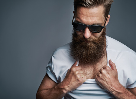 hair man: Single long bearded man in sunglasses showing off his chest by pulling down white shirt collar over gray background