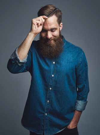 the well groomed: Well groomed handsome bearded man in blue denim shirt looking downward with happy expression while combing his hair over gray background Stock Photo