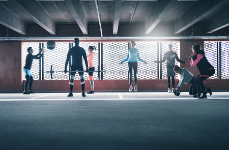 out of town: Group of diverse friends working out in town in a commercial building doing a variety of different exercises weightlifting, skipping and throwing ball