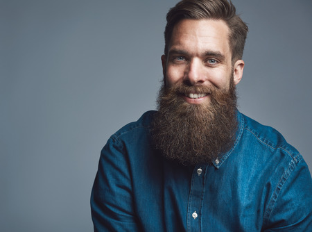 Single sitting young handsome serious man in blue denim shirt and beard over gray background with copy space Archivio Fotografico