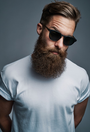 quizzical: Single long bearded man in sunglasses with raised eyebrow and arms behind his back over gray background