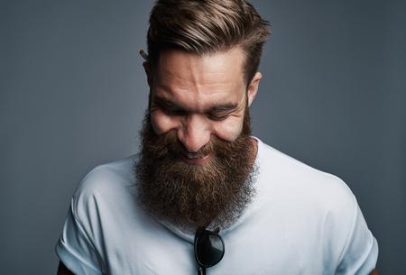 Single giechelen aantrekkelijke jonge Europese man met grote harige baard met bril geplaatst in overhemd over grijze achtergrond