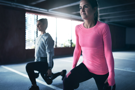 lounges: Two women exercising together using weights doing squat or lounges Stock Photo