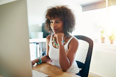 잠겨있는 식으로 화면을 읽고 대형 데스크톱 모니터에서 그녀의 홈 오피스에서 일하고 꽤 젊은 여성 기업가