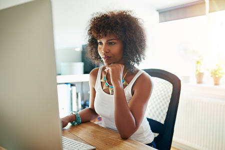 Pretty young female entrepreneur working in her home office at a large desktop monitor reading the screen with a pensive expression