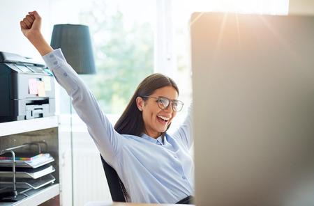 Freudige weibliche Unternehmer in kleinen Büro mit ausgebreiteten Armen, als ob etwas Wunderbares wie ein Geschäft zu feiern