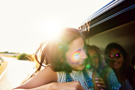 high spirited: Laughing vivacious teenager travelling with friends in a car backlit with the rising summer sun as she leans out of a window to enjoy the breeze Stock Photo