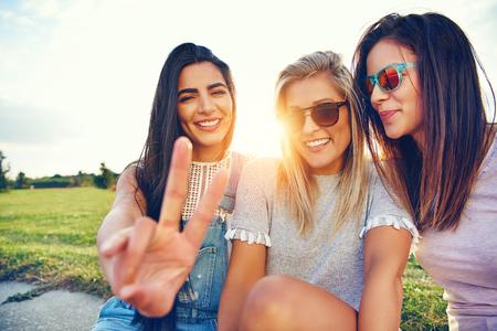 Bezaubernde freundliche junge Frauen, die in einer Gruppe draußen in der Morgensonne sitzen, machen ein V-Zeichen für Frieden oder Sieg Witz süßes Lächeln des Vergnügens