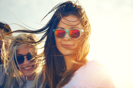 Two gorgeous trendy young women enjoying the breze on a hot summer day standing in their sunglasses smiling at the camera, close up head shot