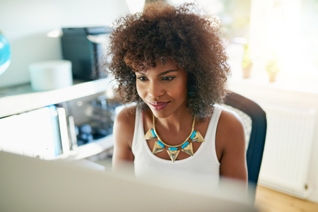 ethnic woman: Attractive young African American woman working on a large desktop computer monitor in a bright sunny office reading the screen with a smile