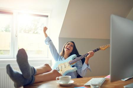 Schitterende vrouw met gitaar die met vreugde schreeuwt terwijl blote voetjes op een bureau naast de computer staan
