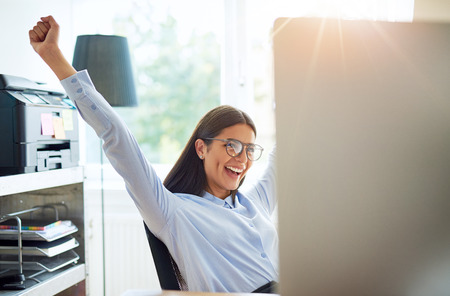 exultant: Joyous female entrepreneur in small office with extended arms as if to celebrate something wonderful such as a business deal