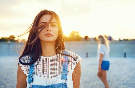 白いブラウスとブルー ジーンズのオーバー オールで美しい若い成人女性の髪を吹く風。バック グラウンドでの日光。 写真素材