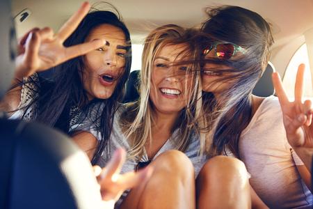 Drie mooie vrouwelijke vrienden maken vredesteken terwijl ze in de achterbank van de auto zitten met wind in hun haar