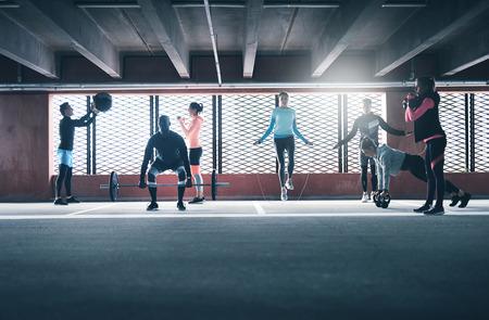 함께 운동하는 사람들의 그룹, 건너 뛰는 밧줄과 의학 공을 사용하여 무게 리프팅