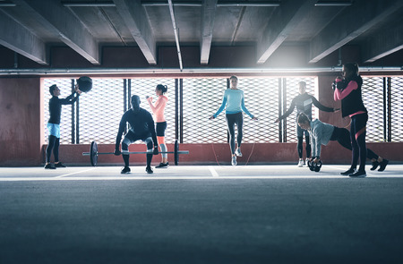 Group of people exercising together, lifting weight using skipping rope and medicine ball
