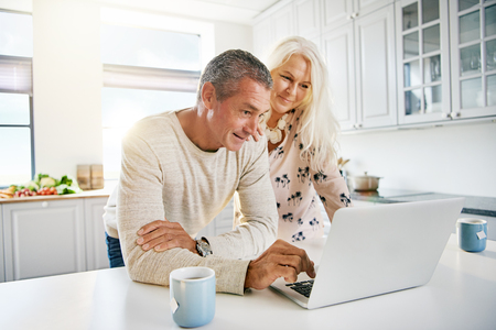 Elderly retired couple reading their social media news on a laptop computer in a fresh white kitchen as they enjoy a relaxing retirement