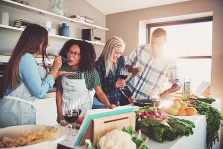 Los buenos amigos degustación de comida en la mesa llena de verduras y pasta listo para cocinar en la cocina
