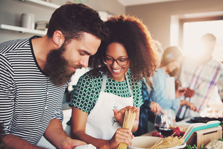 Leuk jong gemengd paar bereiden pasta diner in de keuken met vrienden. Helder zonlicht schijnt door raam. Stockfoto