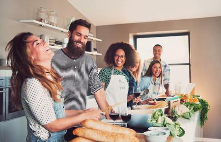 学校でキッチンで一緒にや大きな窓と自宅の食事を準備する美食家のグループ