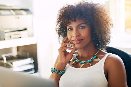 mujer pensativa: Empresario de sexo femenino negro en la oficina sentado en el escritorio sonriendo a la cámara
