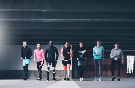 lining up: Group of multiethnic young athletes preparing to run a race through a spacious commercial undercover car park lining up facing the camera in a healthy active lifestyle concept