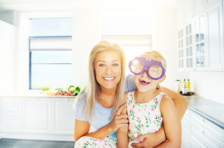 hugged: Vivacious little girl in outsized plastic glasses laughing merrily for the camera as she is hugged by her loving mother Stock Photo