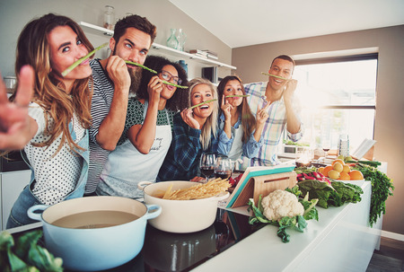 Five friends having a little break to fool around with some asparagus while cooking Stock Photo