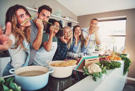 Vijf vrienden met een kleine pauze om rond de gek houden met een aantal asperges tijdens het koken