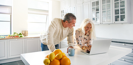 フォア グラウンドで柑橘系の果物の健康的なボウルでインター ネット サーフィンをラップトップ コンピューターで台所で一緒にリラックスできる