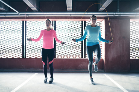 Front view of two athletic girls doing jump rope exercise. Copyspace