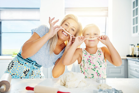 gaiety: Playful Mum and daughter with pastry mustaches baking together in the kitchen preparing a mound of dough, high key background with copy space