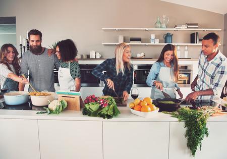 Seis amigos blancos y negros mezclados preparan verduras y pasta en larga mesa en la cocina