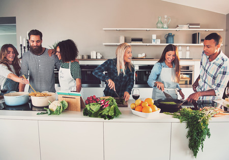 Sześć mieszanych czarno-białe przyjaciół przygotowywania warzyw i makaronu na długi stół w kuchni