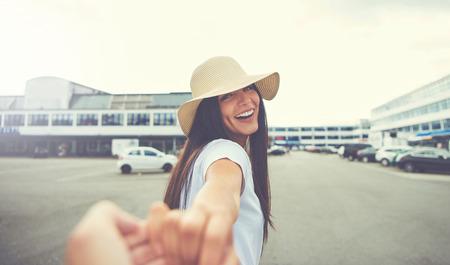 女性の手では、駐車中の車に近い距離を回しながらカメラ笑顔に向けて伸ばしてください。 写真素材