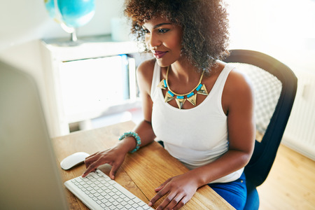 Stylish young African American entrepreneur working from her home office on her website sitting at a desk reading the screen of a large desktop monitor