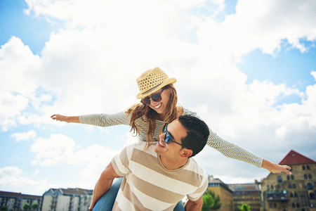 Young couple having fun piggy backing with the laughing young woman holding out her arms pretending to be an airplane as they relax on summer vacation