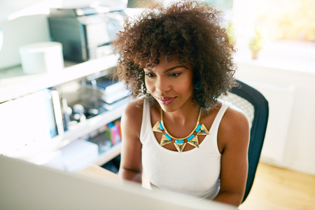 ethnic woman: View of stylish young curly woman working in office. Copyspace Stock Photo
