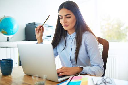 Sola mujer india joven tranquila en blusa azul y cabello largo con lápiz en mano mientras está sentado en el escritorio frente a la computadora portátil en la habitación luminosa